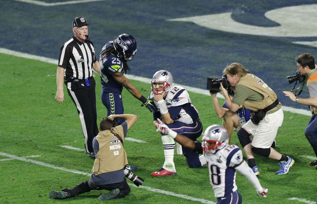 Richard Sherman of the Seattle Seahawks extends a hand of congratulation to Tom Brady, kneeling, of the New England Patriots. The Patriots defeated the Seahawks 28-24 to win Super Bowl XLIX.