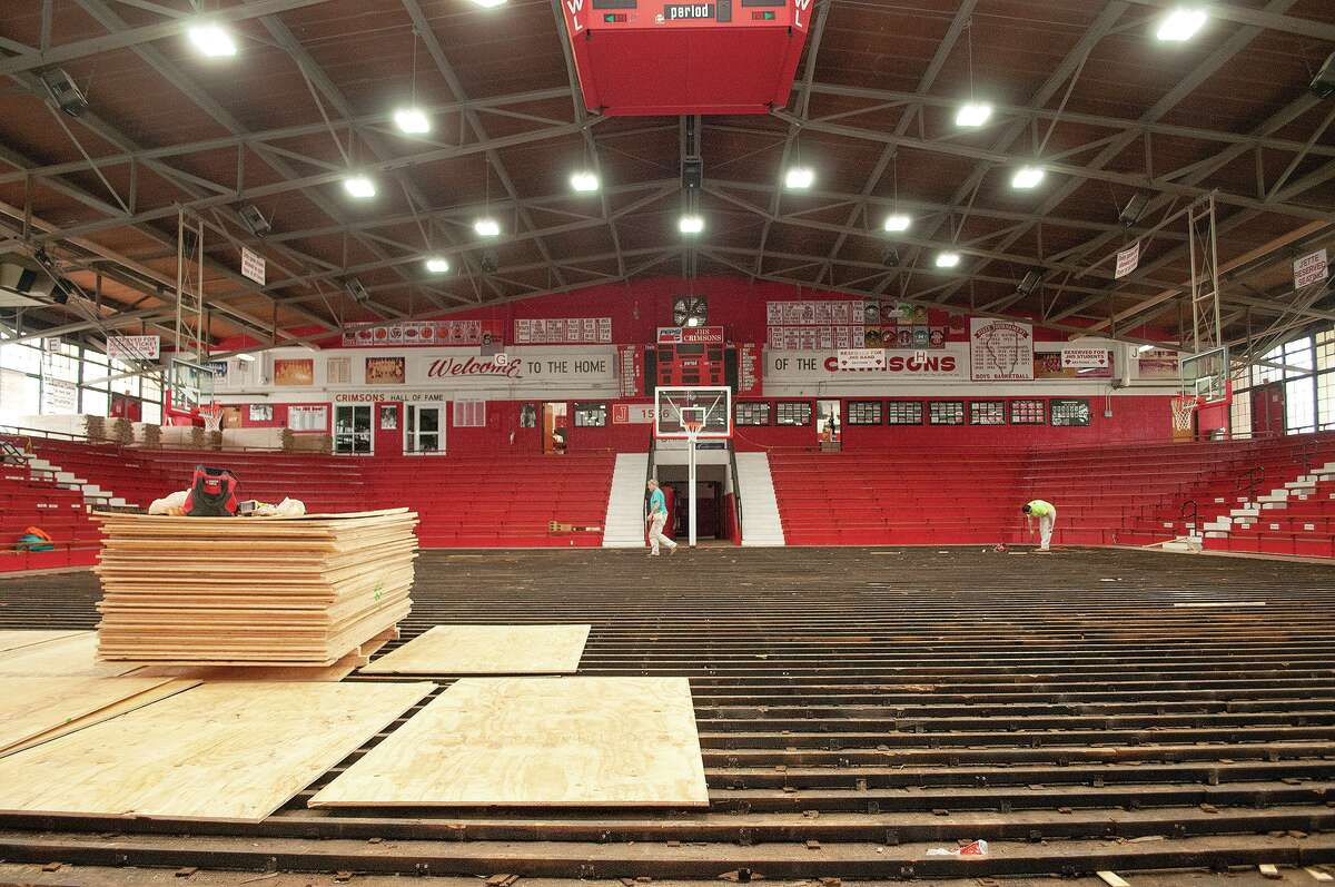Crews work to install new flooring at the JHS Bowl. The project, including staining and adding floor graphics, is expected to to take eight weeks to complete.