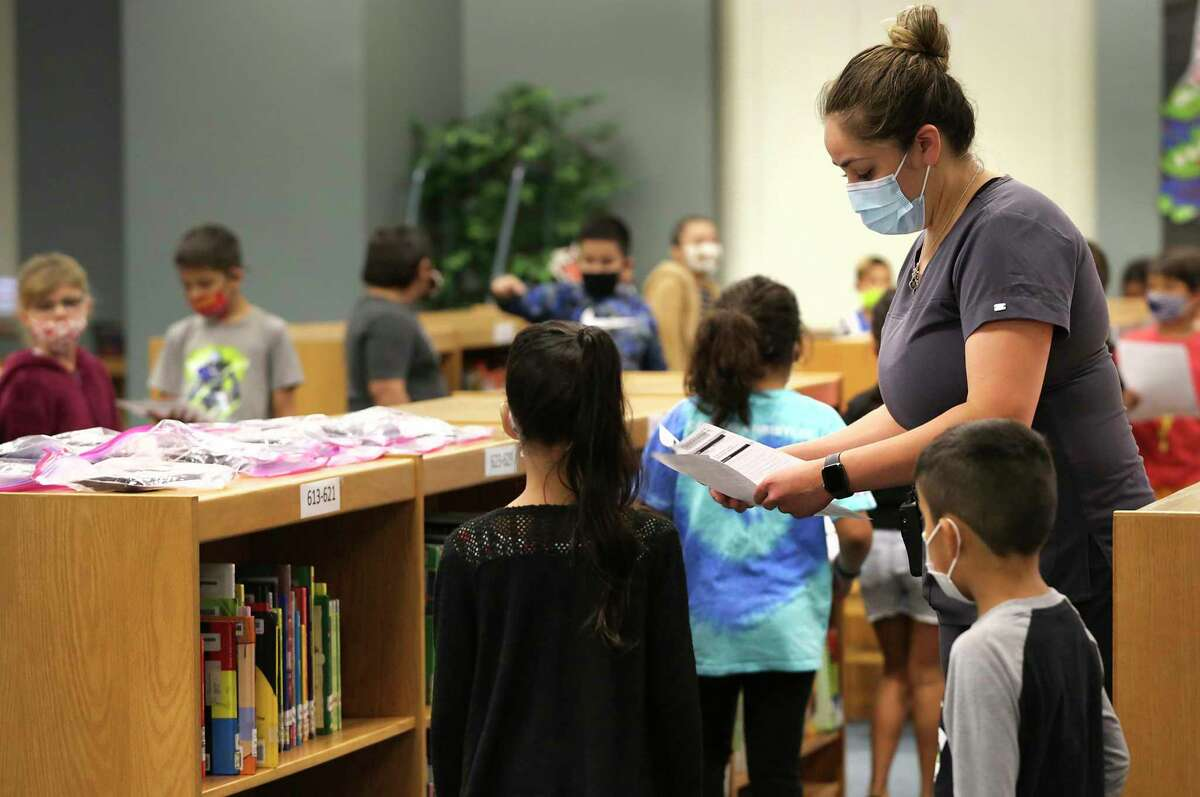 Technicians from Community Labs test staff and students at Barrera Veterans Elementary School in Somerset ISD for the coronavirus Wednesday. Lynn Treff, the school's nurse, checks the permission slips of students before they are tested.