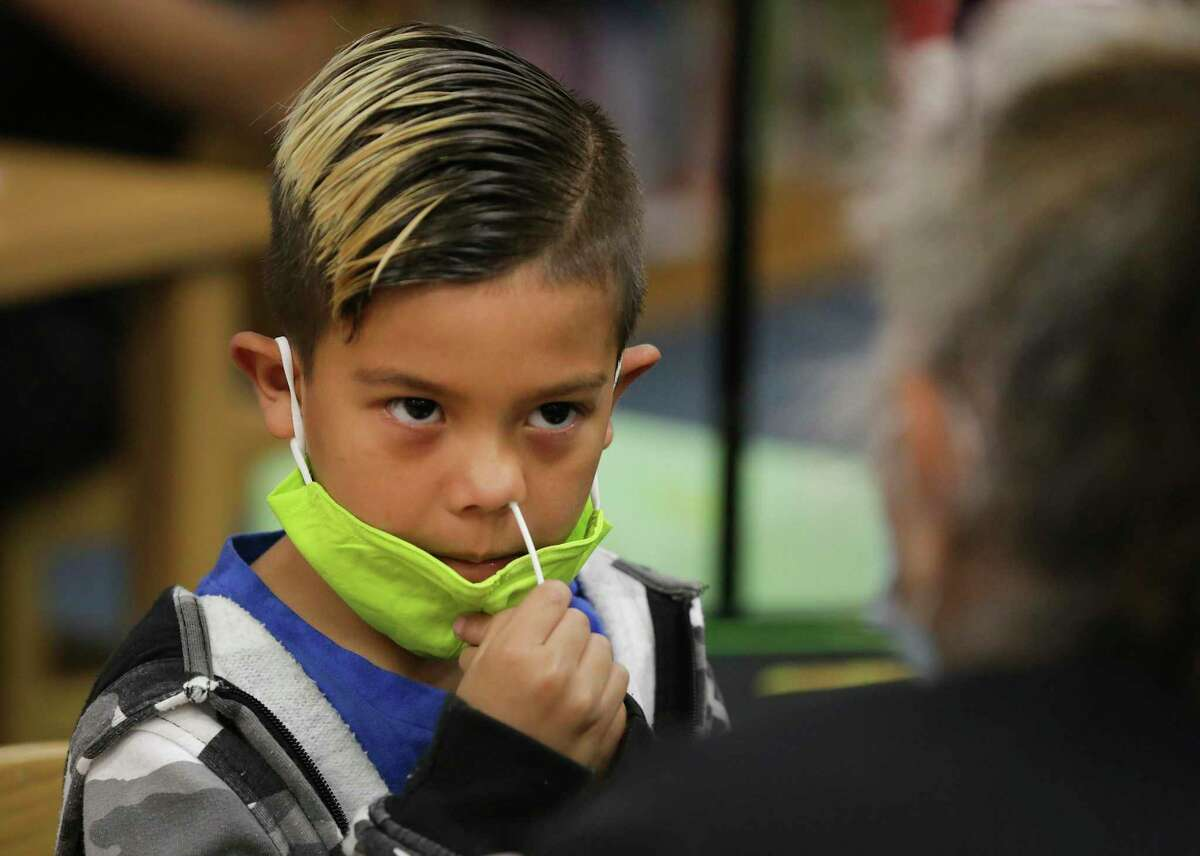 Technicians from Community Labs test staff and students at Barrera Veterans Elementary School in Somerset ISD for the coronavirus on Oct. 21. Harvey Hernandez, a first grader, uses the swab inside his nose during the test.