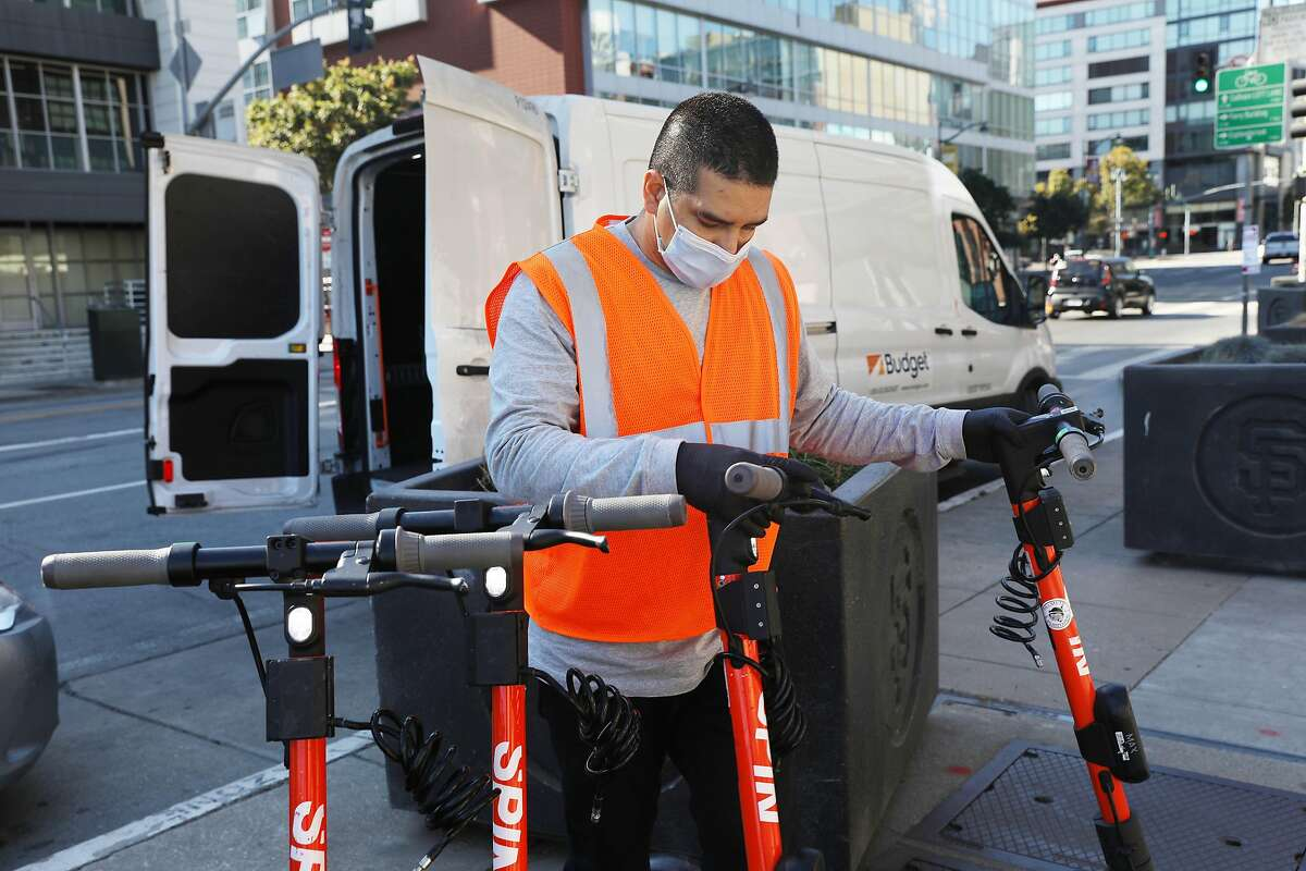 Michael Delgado, SPIN operations specialist, unloads SPIN scooters from a van while deploying scooters at Oracle Park on Monday, October 19, 2020 in San Francisco, Calif.