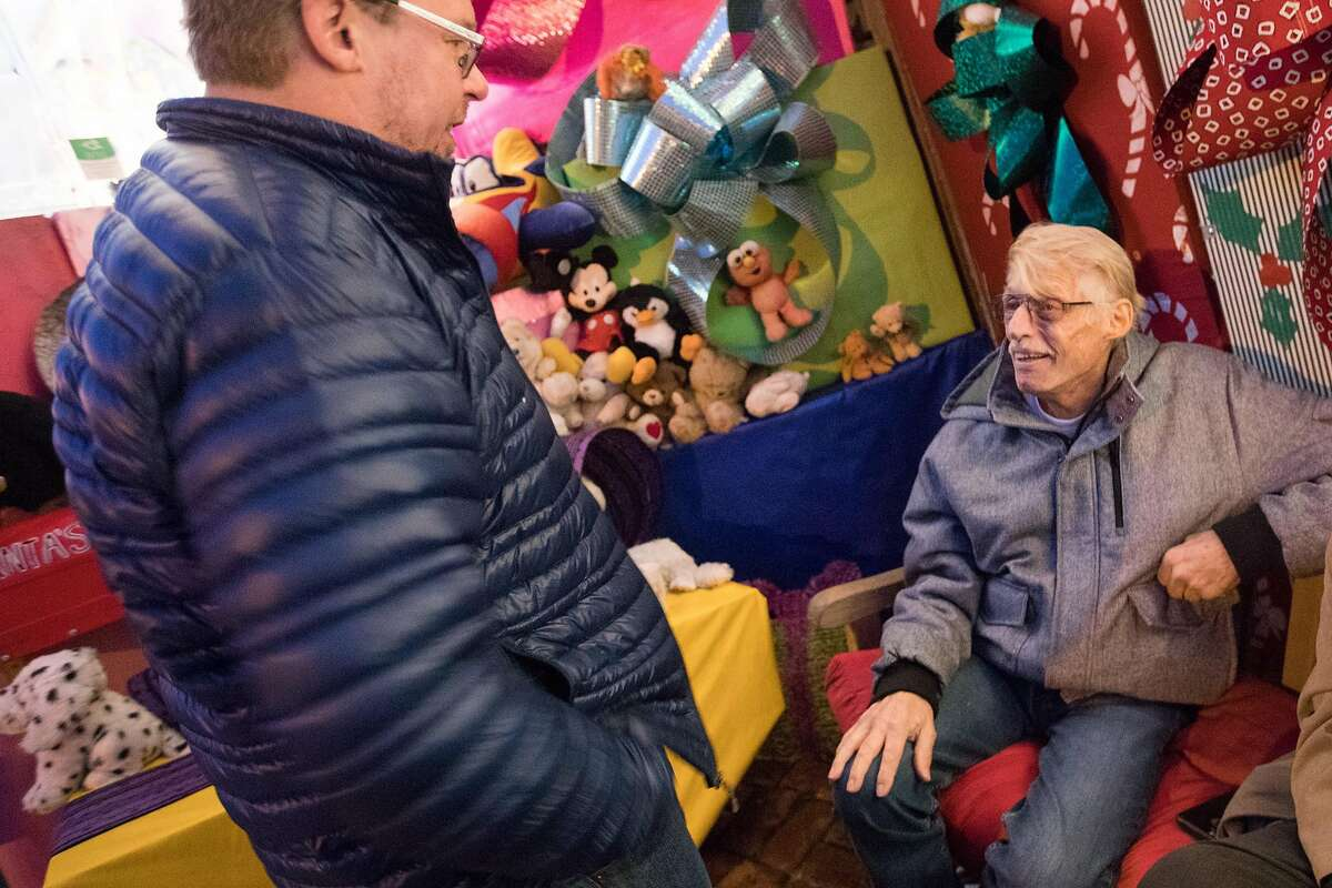 Tom Taylor speaks with a visitor outside his holiday-decorated house in San Francisco on Dec. 15, 2019. For years, Tom and his husband Jerome