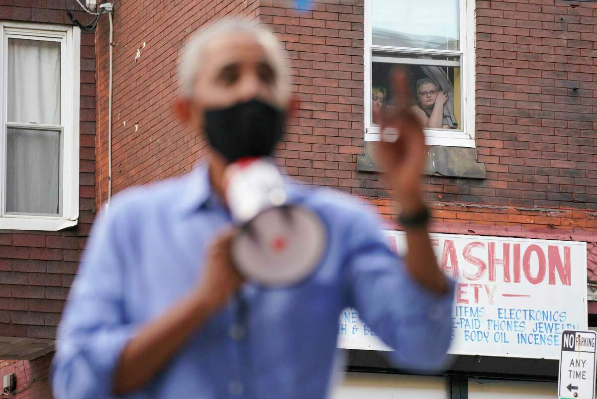 Women watch from a window as former president Barack Obama campaigns in Philadelphia on Wednesday for Democratic nominee Joe Biden.