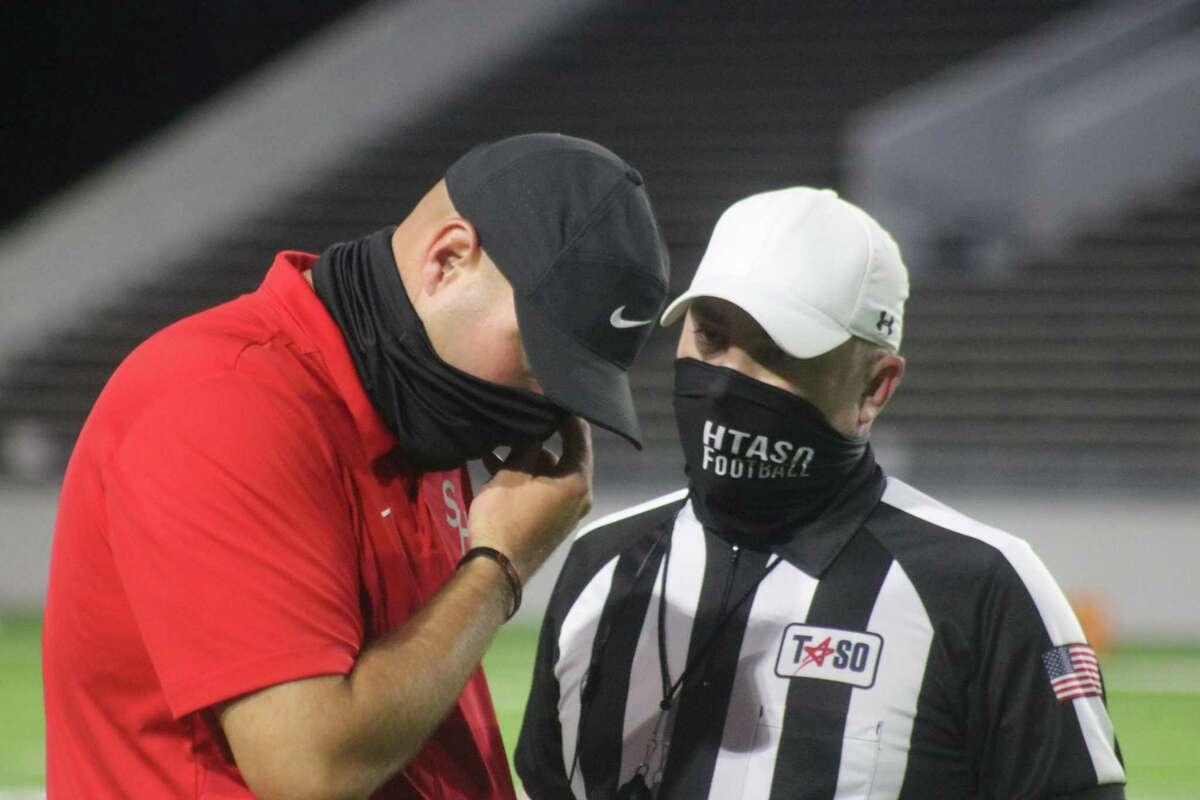 South Houston head football coach Patrick Longstreet receives an explanation about a call in a game earlier this season. He hopes there won't be any meetings with refs Thursday night as the Trojans look to cut down on their penalties.