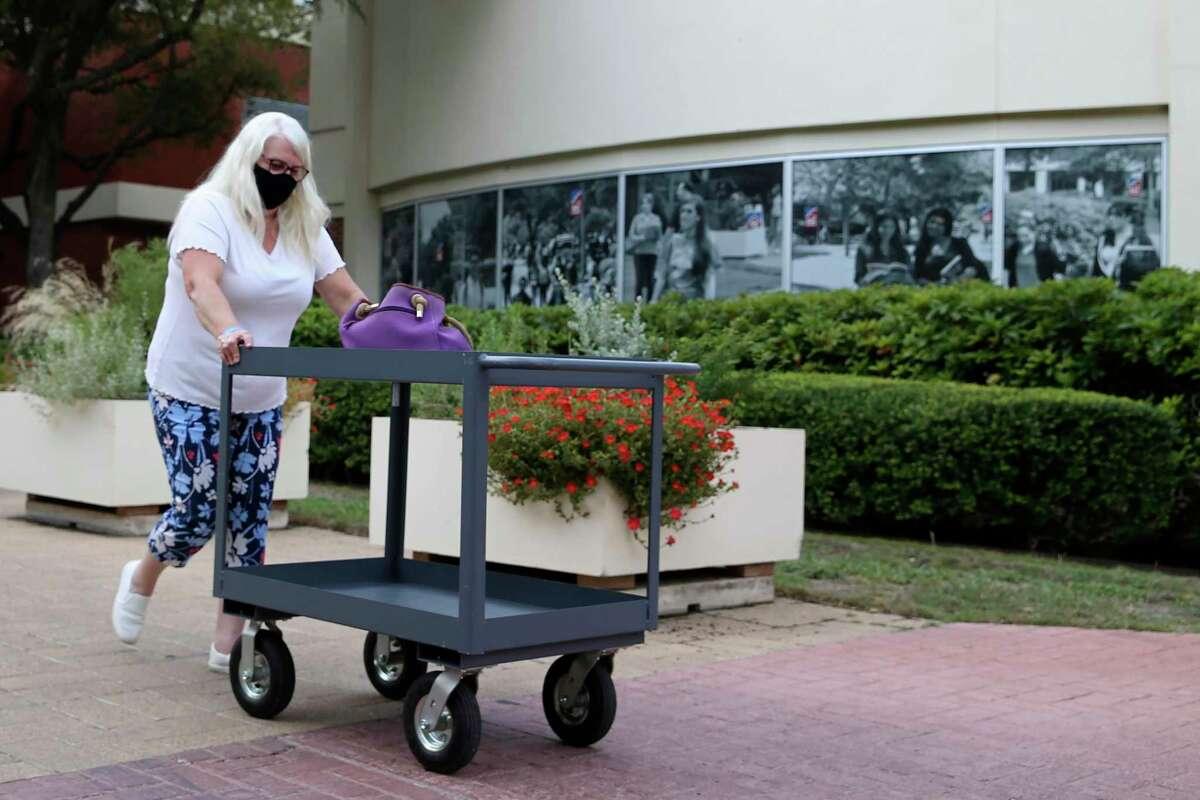 IT worker Cheri Sanchez walks between departments at San Antonio College on Tuesday.