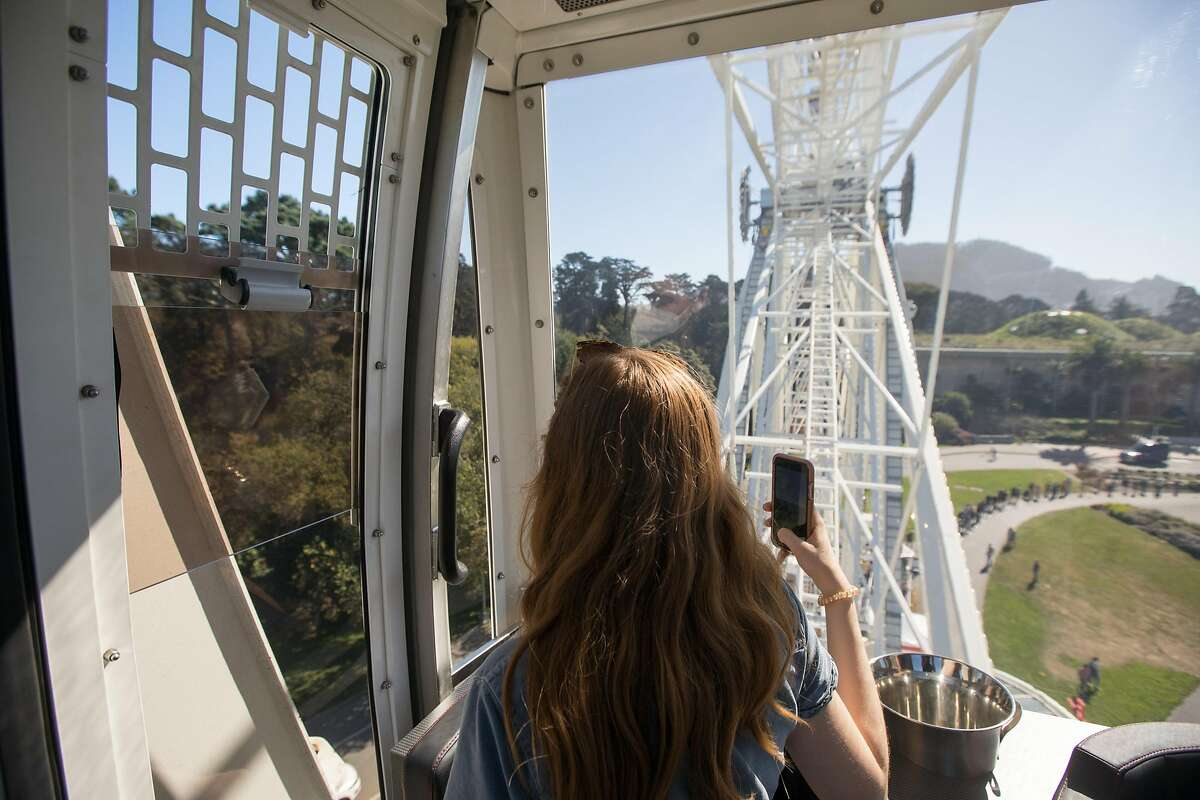 A passenger takes in the view from a SkyStar Observation Wheel gondola on its opening day at the Golden Gate Park Music Concourse in San Francisco, California on October 21, 2020.