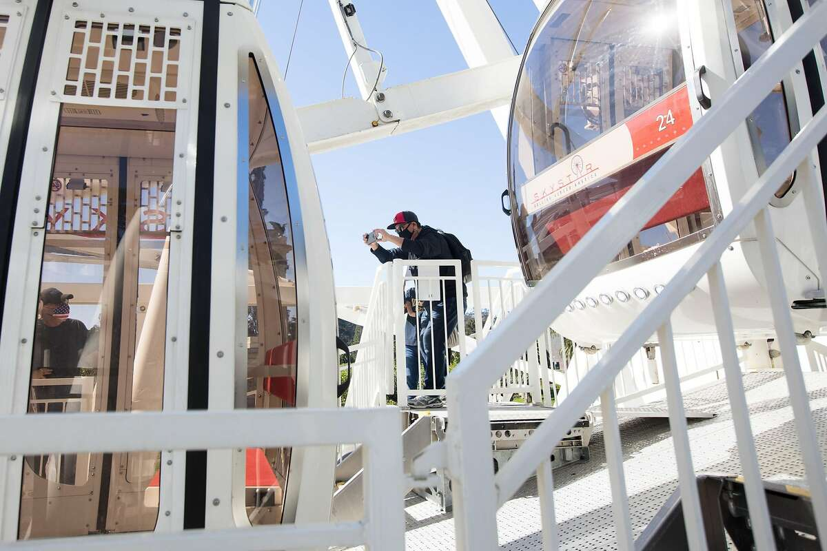 A waiting passenger takes the photo of the SkyStar Observation Wheel as it opened to the public at the Golden Gate Park Music Concourse in San Francisco, California on October 21, 2020.