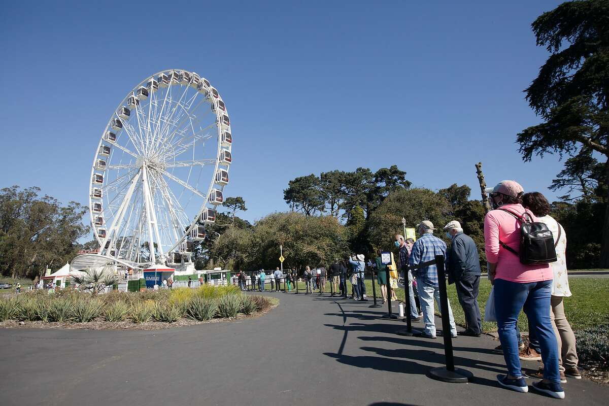 Ticket holders line up for a ride on the SkyStar Observation Wheel on the opening day to the public at the Golden Gate Park Music Concourse in San Francisco, California on October 21, 2020.