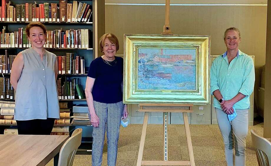 From left, Maggie Dimock, Susan Larkin and Lily Downing showcase the recently acquired 1896 Childe Hassam painting The Red Mill, Cos Cob. It will be displayed by the Greenwich Historical Society. Photo: Greenwich Historical Society