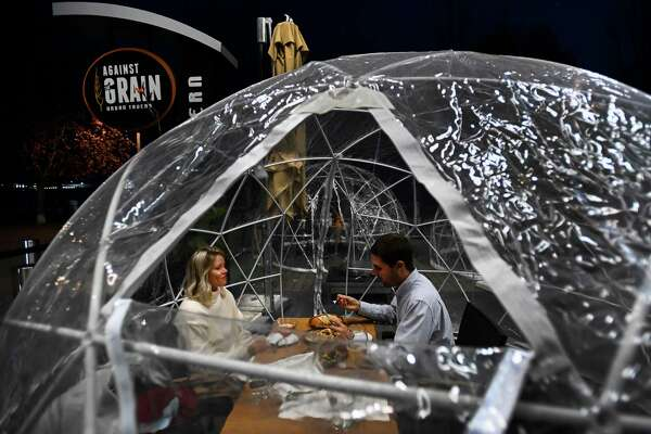 People enjoy outdoor dining in a weather proof dome pod at Against the Grain Urban Tavern during the COVID-19 pandemic in Toronto on Wednesday, Oct. 21, 2020. (Nathan Denette/The Canadian Press via AP)