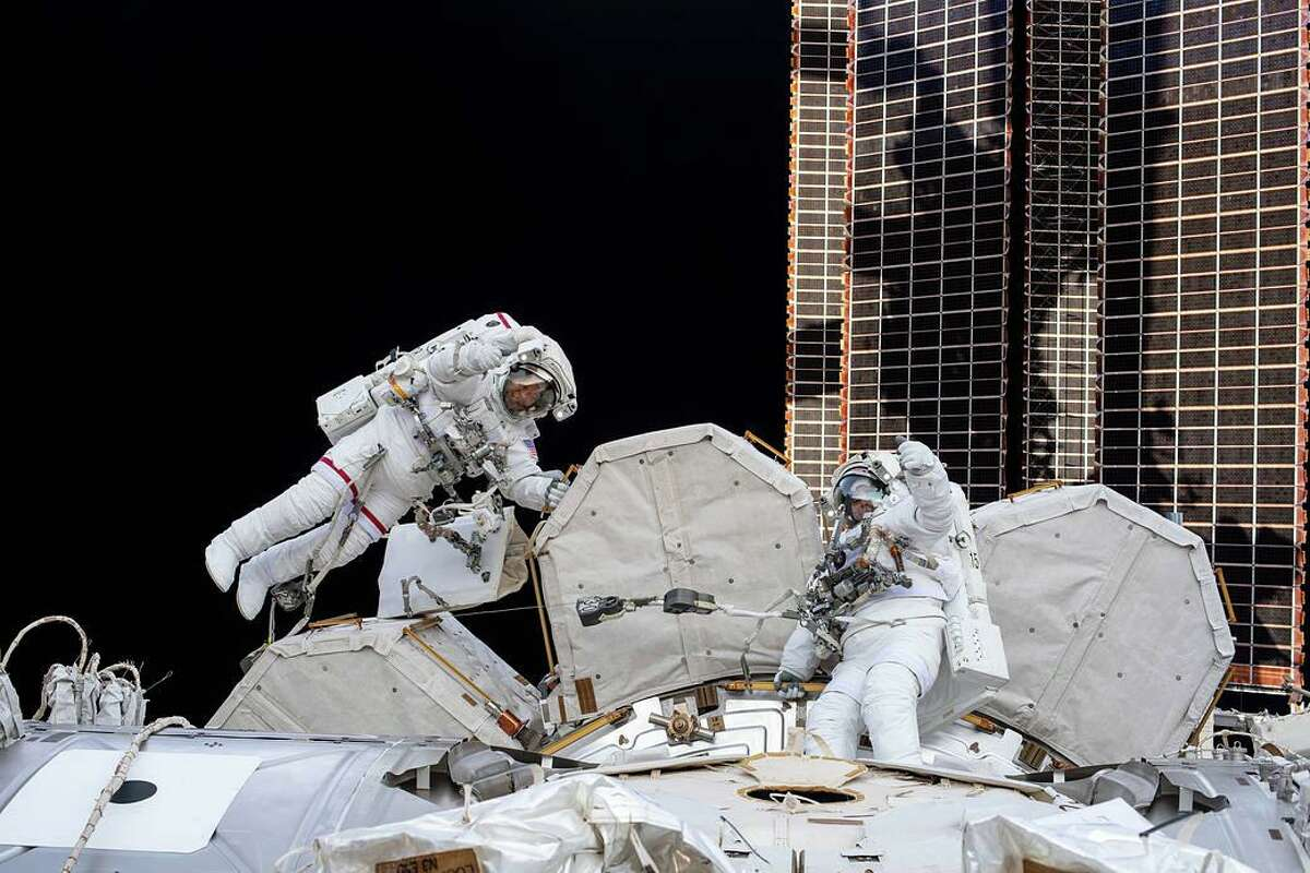 Astronauts Bob Behnken and Chris Cassidy give a thumbs up during a July 2020 spacewalk to install hardware and upgrade International Space Station systems.