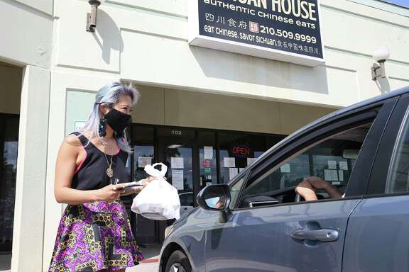 Sichuan House owner Kristina Zhao carries a takeout order to a customer. The business ramped up its takeout and delivery services to stay afloat during COVID-19.