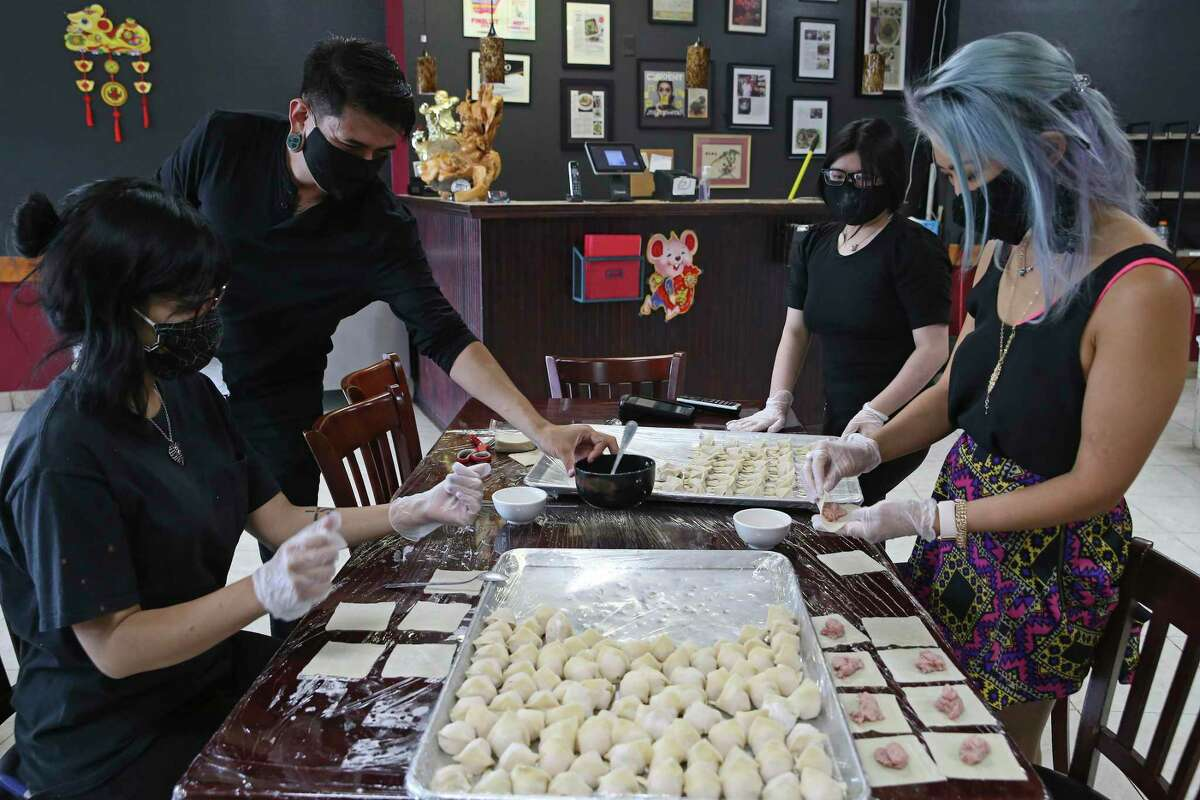 Owner Kristina Zhao, right, prepares wontons with her staff at Sichuan House, jumping in to help as the restaurant deals with the takeout and delivery demand created by the pandemic. With her are from left, Erica Romero, Brandon Hernandez and Cindy Bo.