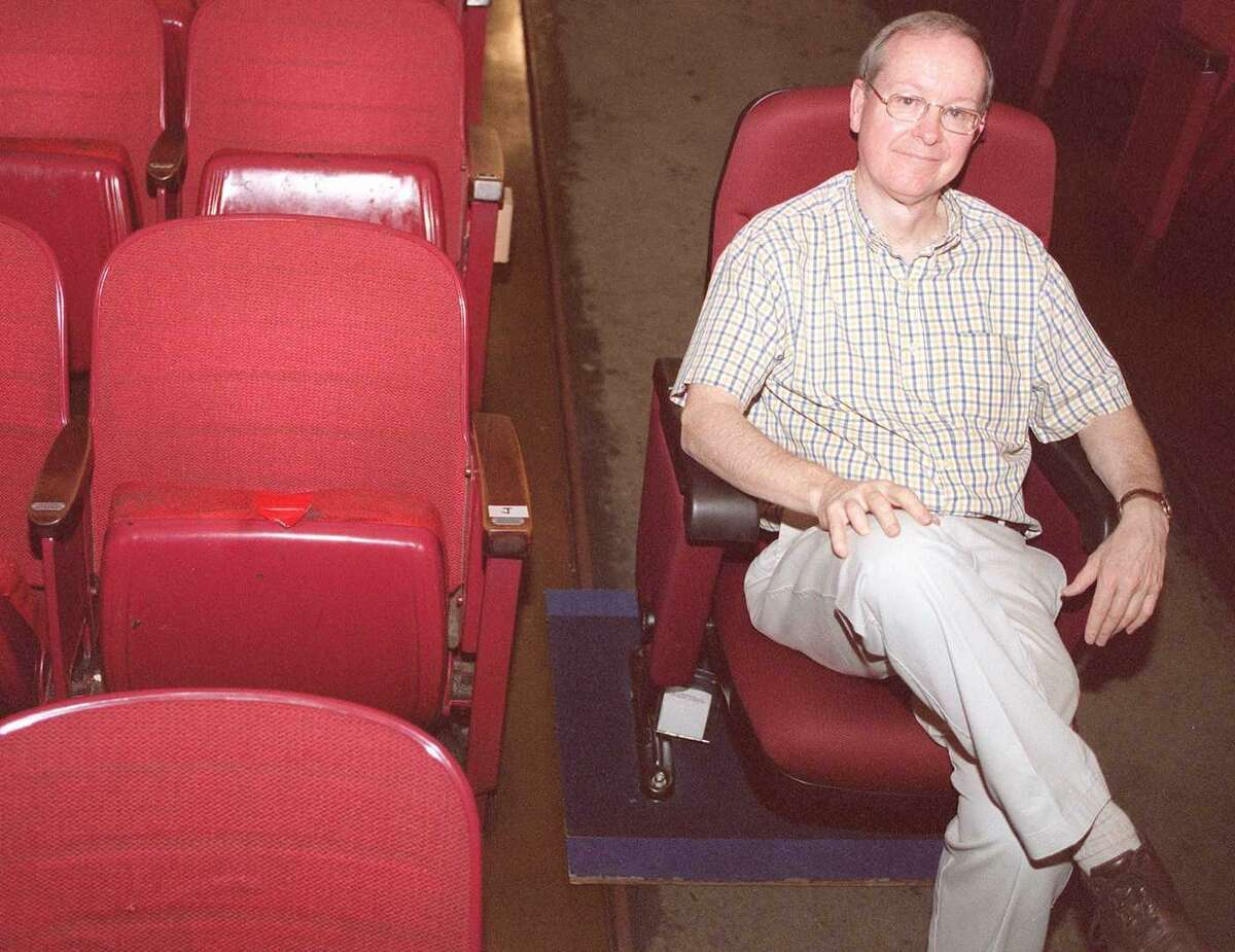 Edmond Town Hall Theatre Manager Tom Mahoney models a new seat for the theatre, next to one of the theatre's old seats, which have not been upgraded since the 1960's