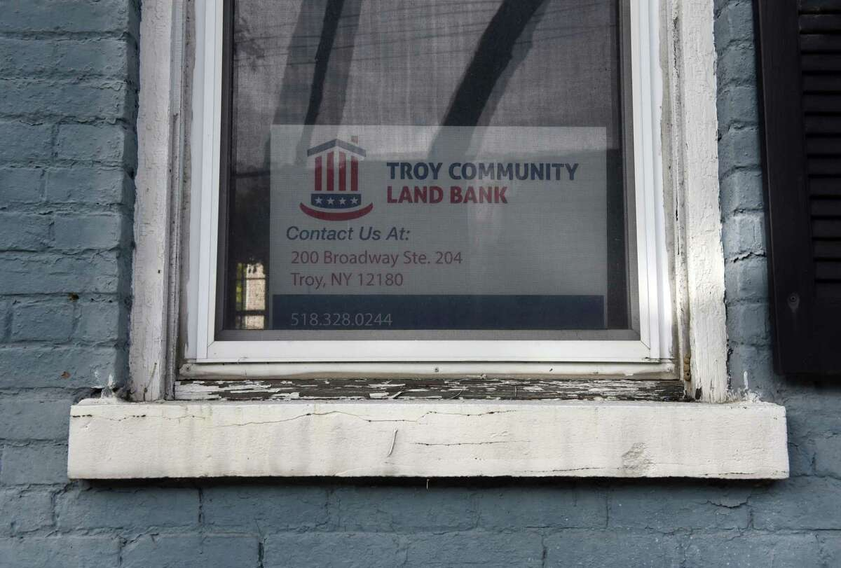 A Troy Community Land Bank sign is posted in a front window at 3325 Sixth Avenue on Thursday, Oct. 22, 2020, in Troy, N.Y. The city intends to restore the property for $80,000 under its zombie program. (Will Waldron/Times Union)