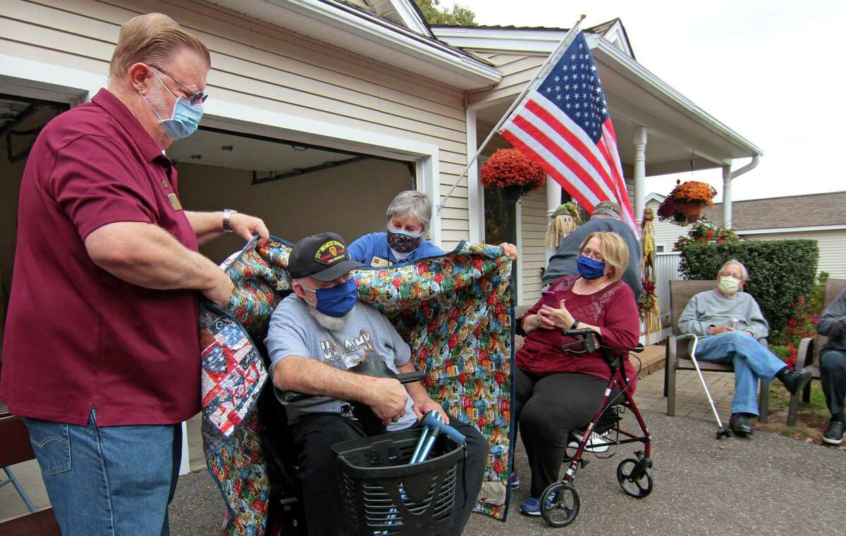 Vietnam veteran Steve Urban, center, is wrapped with a hand made quilt by Quilts of Valor Foundation representatives Chuck Larkins, left, and Jane Dougherty at his home in Seymour, Conn., on Wednesday Oct. 21, 2020. The Agency on Aging also helped make the honor possible.