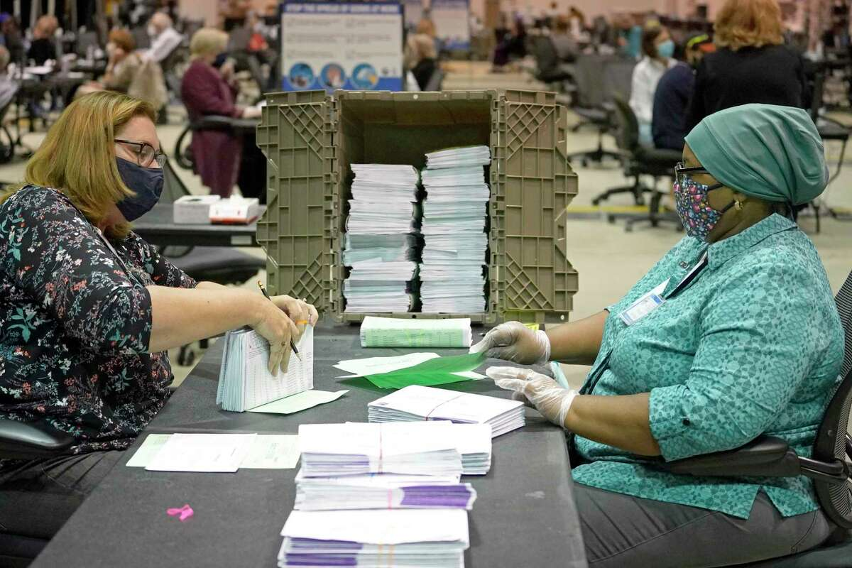 Members of the signature verification committee work on processing mail in ballots at NRG Arena Wednesday, Oct. 21, 2020 in Houston.