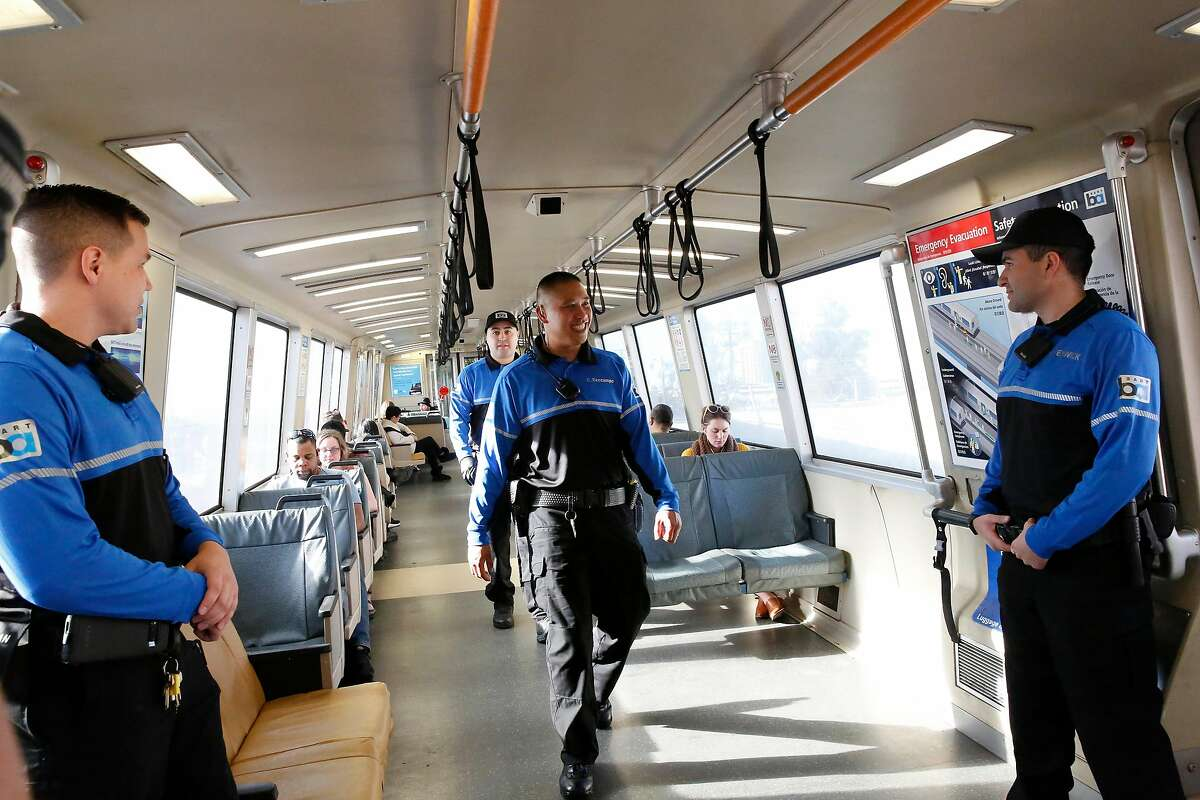 BART ambassadors Dontaye Romero (center left) and Ceasar Deocampo (center right) walk through a BART train as BART ambassadors Malakai Cheney (left) and Brandon Fenwick (right) stand near doors while they all work on a BART train on Monday, February 10, 2020 in Oakland, Calif.
