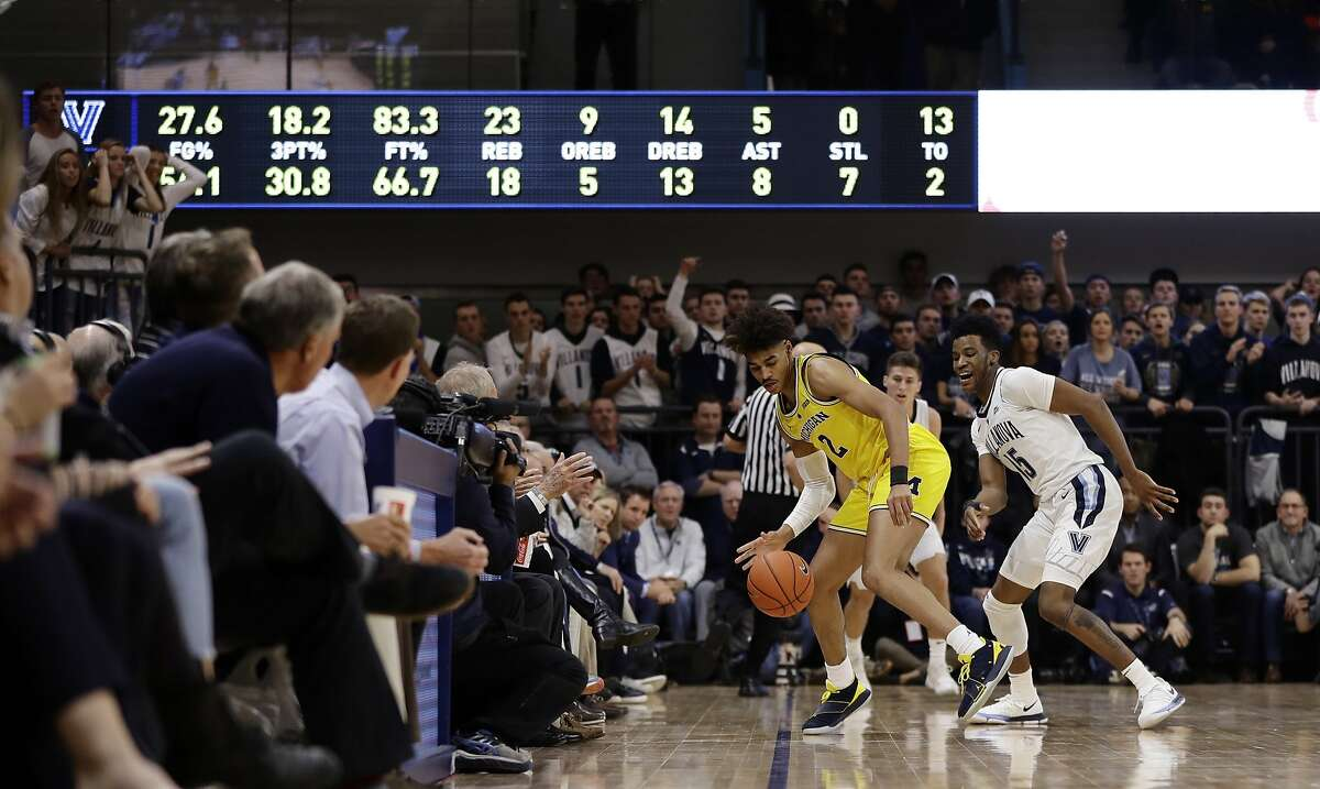 Michigan's Jordan Poole, left, tries to dribble past Villanova's Saddiq Bey during the second half of an NCAA college basketball game, Wednesday, Nov. 14, 2018, in Villanova, Pa. Michigan won 73-46. (AP Photo/Matt Slocum)