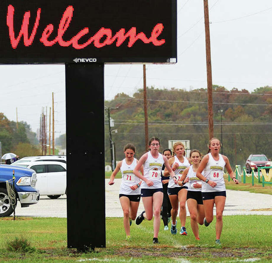 Five Roxana Shells pass the main entrance at Southwestern High School during the second mile of the South Central Conference girls cross country meet Monday in Piasa. Those five Shells finished 1-2-3-4-5 for a perfect score of 15 to win their third consecutive SCC championship. Photo: Greg Shashack / The Telegraph