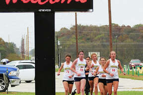 Five Roxana Shells pass the main entrance at Southwestern High School during the second mile of the South Central Conference girls cross country meet Monday in Piasa. Those five Shells finished 1-2-3-4-5 for a perfect score of 15 to win their third consecutive SCC championship.