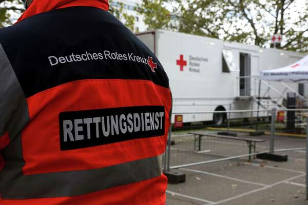 A member of Germany's Red Cross stands near a Covid-19 mobile testing unit as travelers are tested in Berlin, Germany, on Oct. 12, 2020.