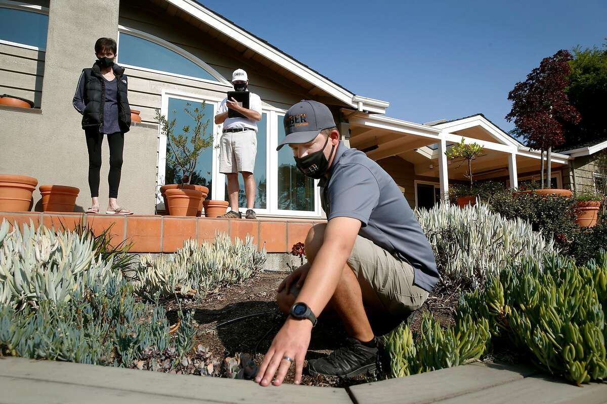 Ember Defense co-founders Devan LeBlanc (right) and Adam Iveson (center) describe wildfire prevention measures to a homeowner in Portola Valley.