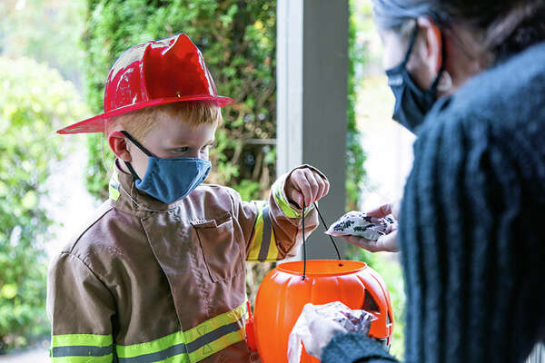 Boy wearing firefighter costume receiving candy on Halloween.