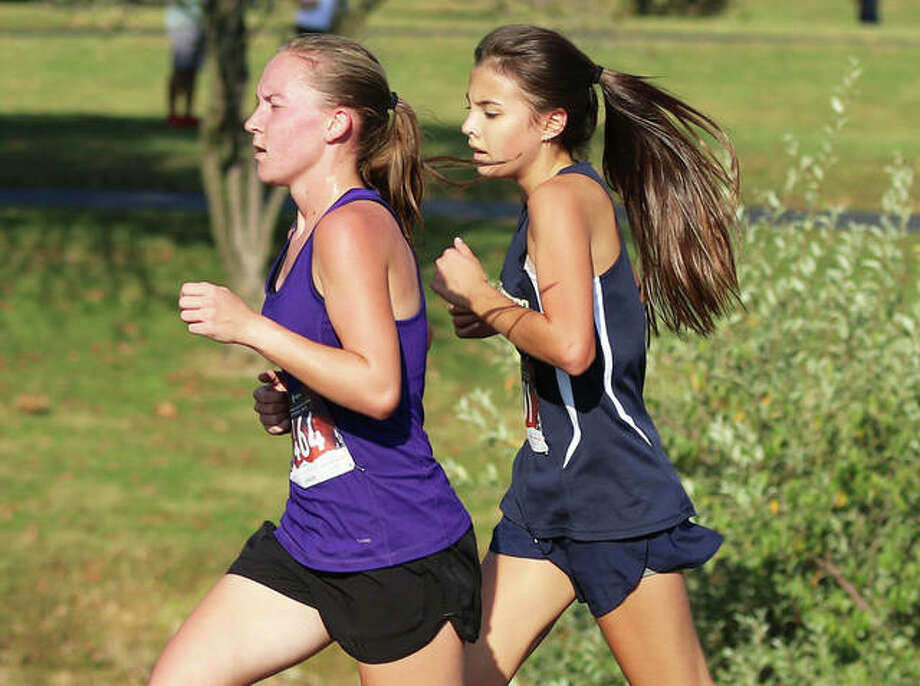 Father McGivney freshman Kaitlyn Hatley (right) draws even with front-runner Hannah Meiser of Civic Memorial in the final half-mile of the Madison County Meet on Oct. 6 at Belk Park in Wood River. Meiser won the race, finishing one-tenth second ahead of Hatley. Photo: Greg Shashack / The Telegraph