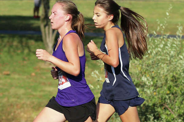 Father McGivney freshman Kaitlyn Hatley (right) draws even with front-runner Hannah Meiser of Civic Memorial in the final half-mile of the Madison County Meet on Oct. 6 at Belk Park in Wood River. Meiser won the race, finishing one-tenth second ahead of Hatley.