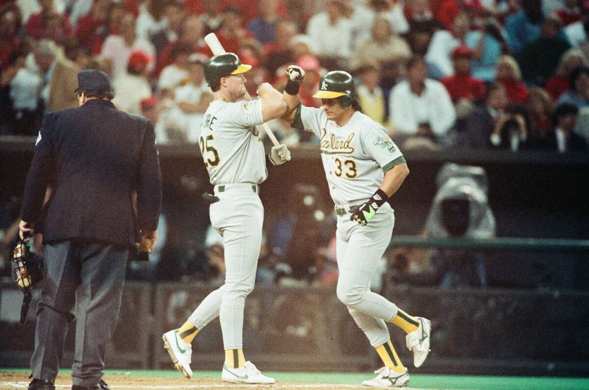 Jose Canseco and Mark McGwire of the Oakland Athletics celebrate Canseco's home run during Game 2 of the 1990 World Series against the Cincinnati Reds at Riverfront Stadium in Cincinnati, Ohio.