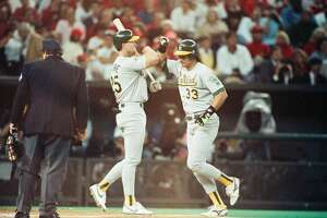CINCINNATI, OH - 1990: Jose Canseco and Mark McGwire of the Oakland Athletics celebrate during the 1990 World Series against the Cincinnati Reds at Riverfront Stadium in Cincinnati, Ohio. (Photo by Sporting News via Getty Images via Getty Images)