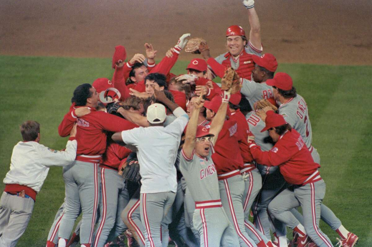 Reds Chris Sabo, front, and catcher Joe Oliver, background, celebrate on the home field of the Oakland A's after beating them 2-1 to win the fourth straight game and the World Series.
