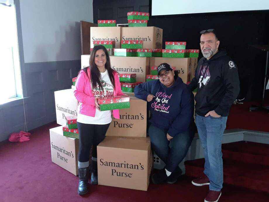 In 2019, Friendship Baptist Church members Rayna Flores, Ivettliz Cotto and youth minister Rob Morzella showed their collection of shoeboxes, packed with gifts, for Operation Christmas Child. The church was a dropoff point for the boxes, and has received many contributions from area churches. This year's Operation Christmas Child effort is inviting groups and churches to sign up. Photo: Emily M Olson / Hearst Connecticut Media /
