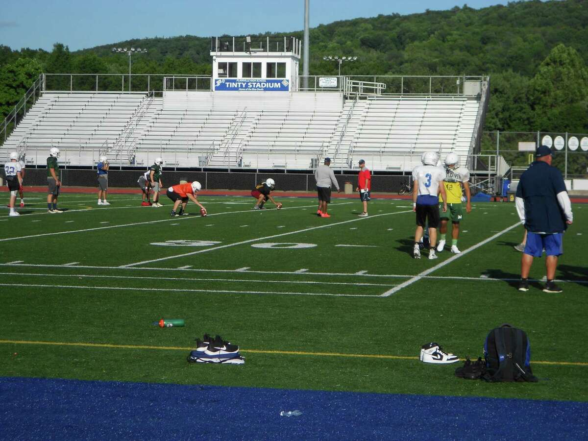 Players and coaches practice football at Veterans Stadium last year in New Britain.