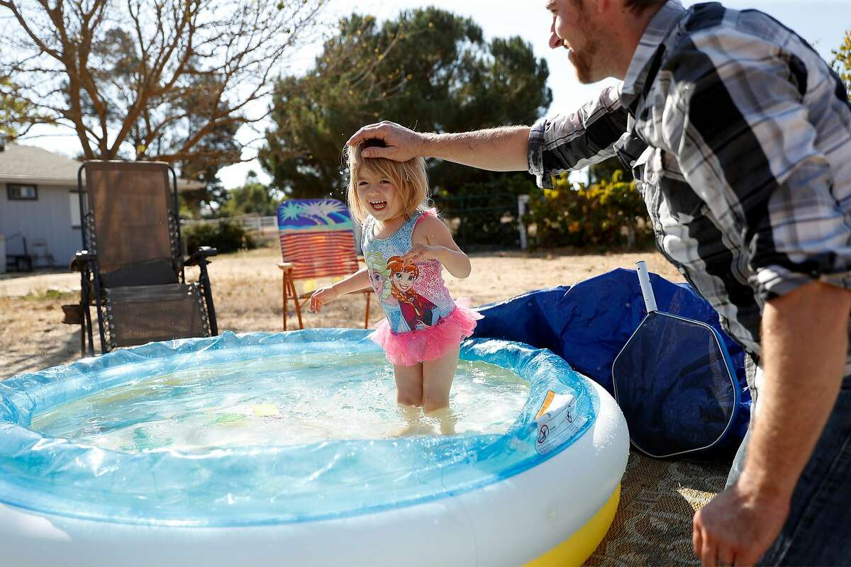 Michael Michalske plays with his daughter, Fiona, at his in-laws' home in San Luis Obispo County. After he was laid off from his stagehand job, he and his wife moved the family from Brisbane to save money.