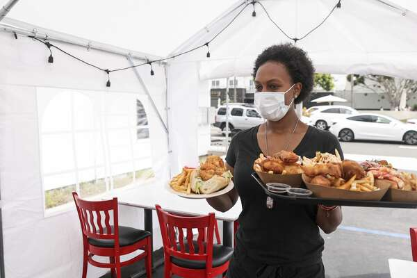 A young black woman serves food to customers sitting inside a tent. She is wearing a mask
