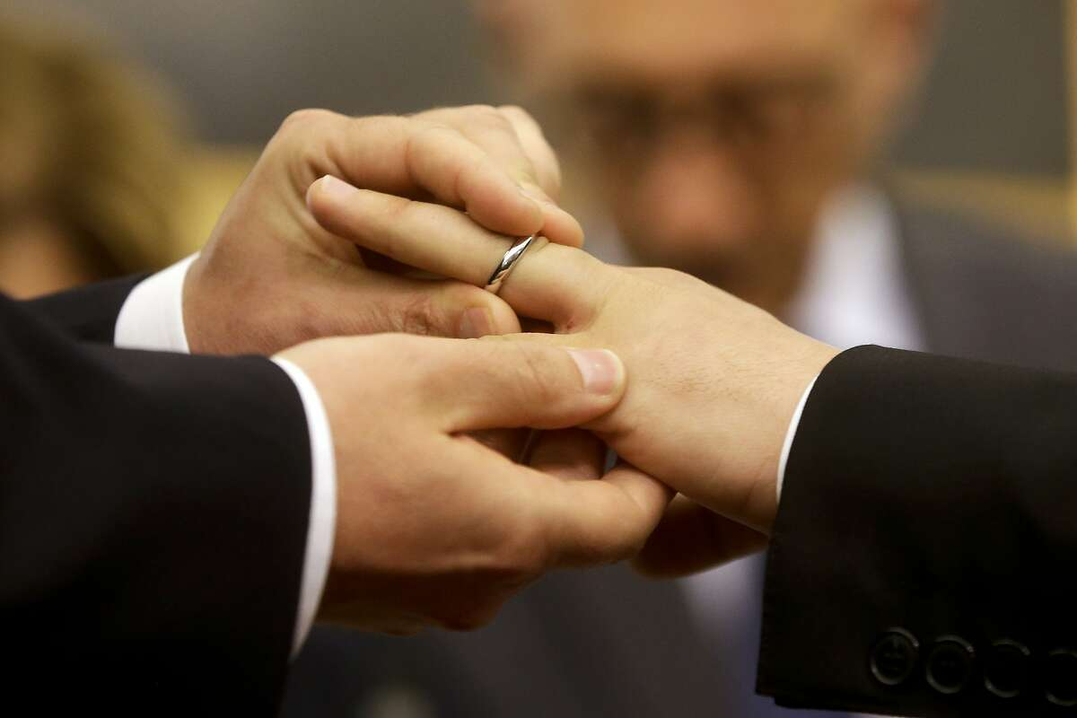 FILE - In this May 21, 2015 file photo, Mauro Cioffari, left, puts a wedding ring on his partner Davide Conti's finger as their civil union is being registered by a municipality officer during a ceremony in Rome's Campidoglio Capitol Hill. Pope Francis endorsed same-sex civil unions for the first time as pope while being interviewed for the feature-length documentary