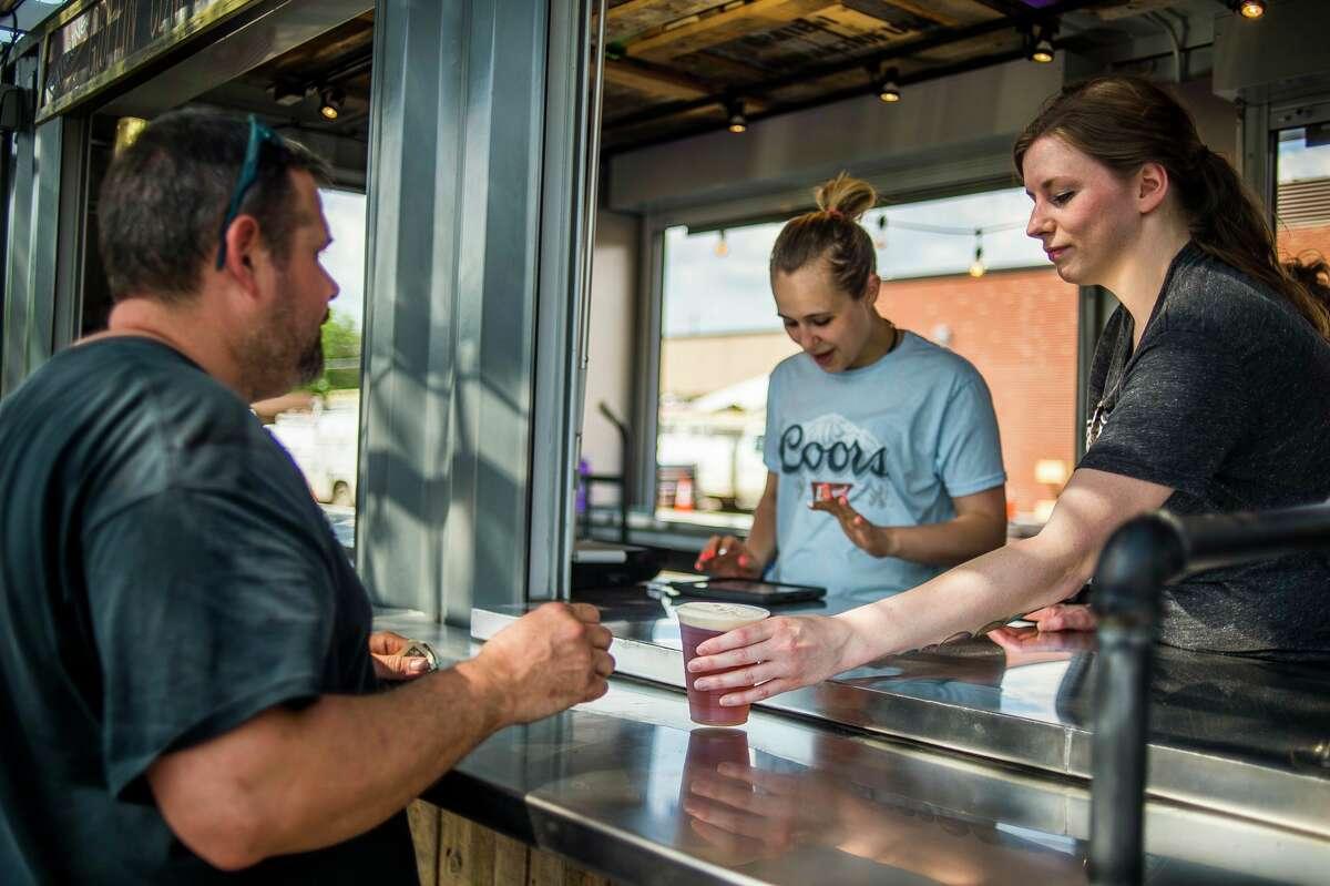 Gena Sasse of Midland, right, serves a beer to a customer at the Larkin Beer Garden Thursday, May 31, 2018. (Katy Kildee/kkildee@mdn.net)