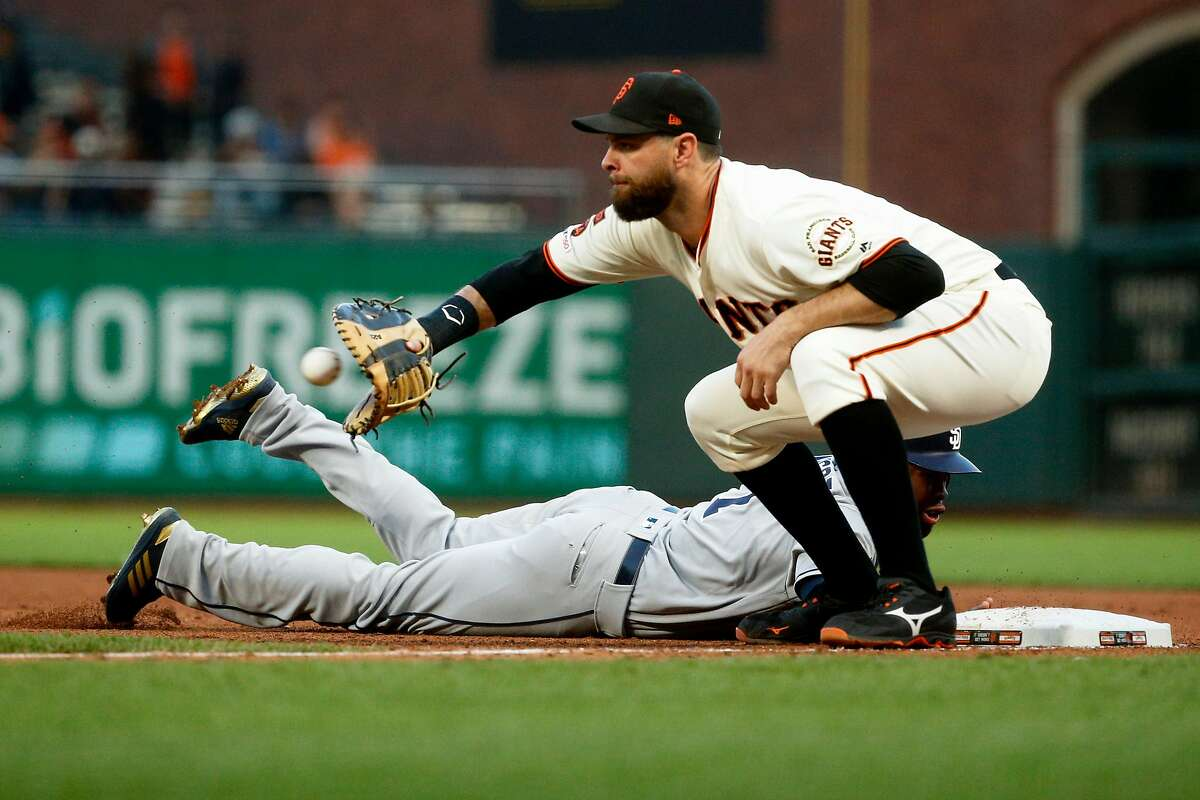 San Diego Padres center fielder Manuel Margot (7) is safe after diving to first base against San Francisco Giants first baseman Brandon Belt (9) in the fifth inning during an MLB game at Oracle Park on Wednesday, June 12, 2019, in San Francisco, Calif.