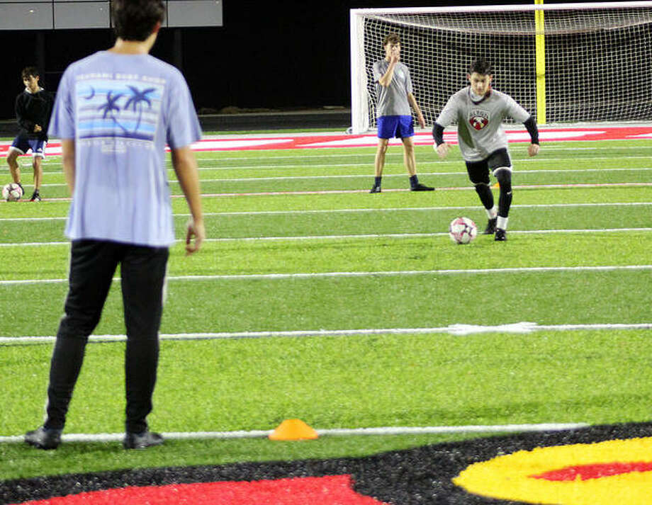 Alton High soccer player Owen Macias dribbles the soccer ball during a drill Wednesday night on the new artificial turf at Public School Stadium. Behind Macias is Sam Clark. Justin Davison's back is in the foreground.. Photo: Pete Hayes | The Telegraph
