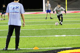 Alton High soccer player Owen Macias dribbles the soccer ball during a drill Wednesday night on the new artificial turf at Public School Stadium. Behind Macias is Sam Clark. Justin Davison's back is in the foreground..