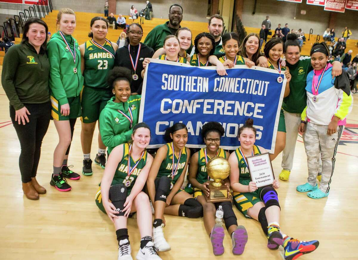 (John Vanacore/for Hearst Connecticut Media) The Hamden girls basketball team celebrate their 40-36 win over East Haven for the SCC Championship title.