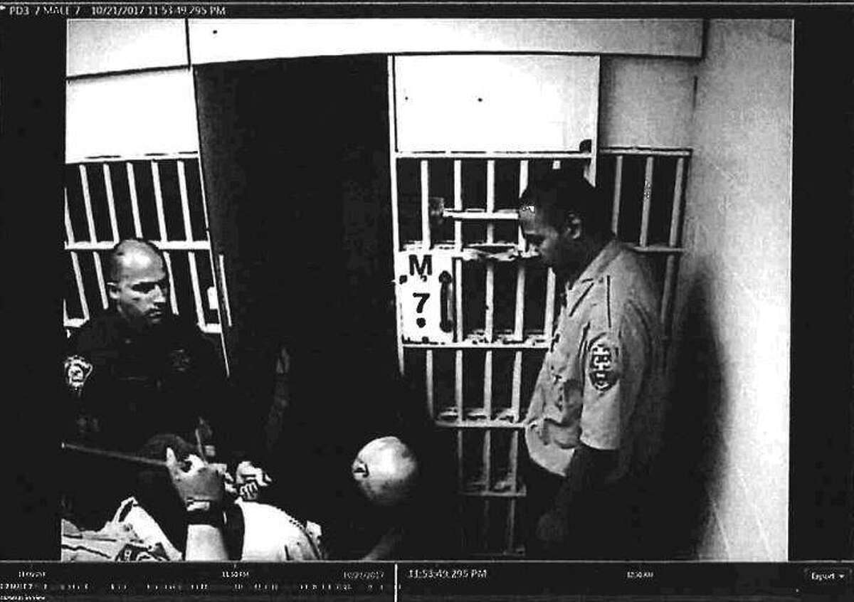 """This photo released in the Bridgeport Police Department's Internal Affairs investigation shows """"Civilian Dentention [sic] Jose Figeroa poking Mr. [Peter] Diaz on the chest in front of male cell 7,"""" on Oct 21, 2017."""