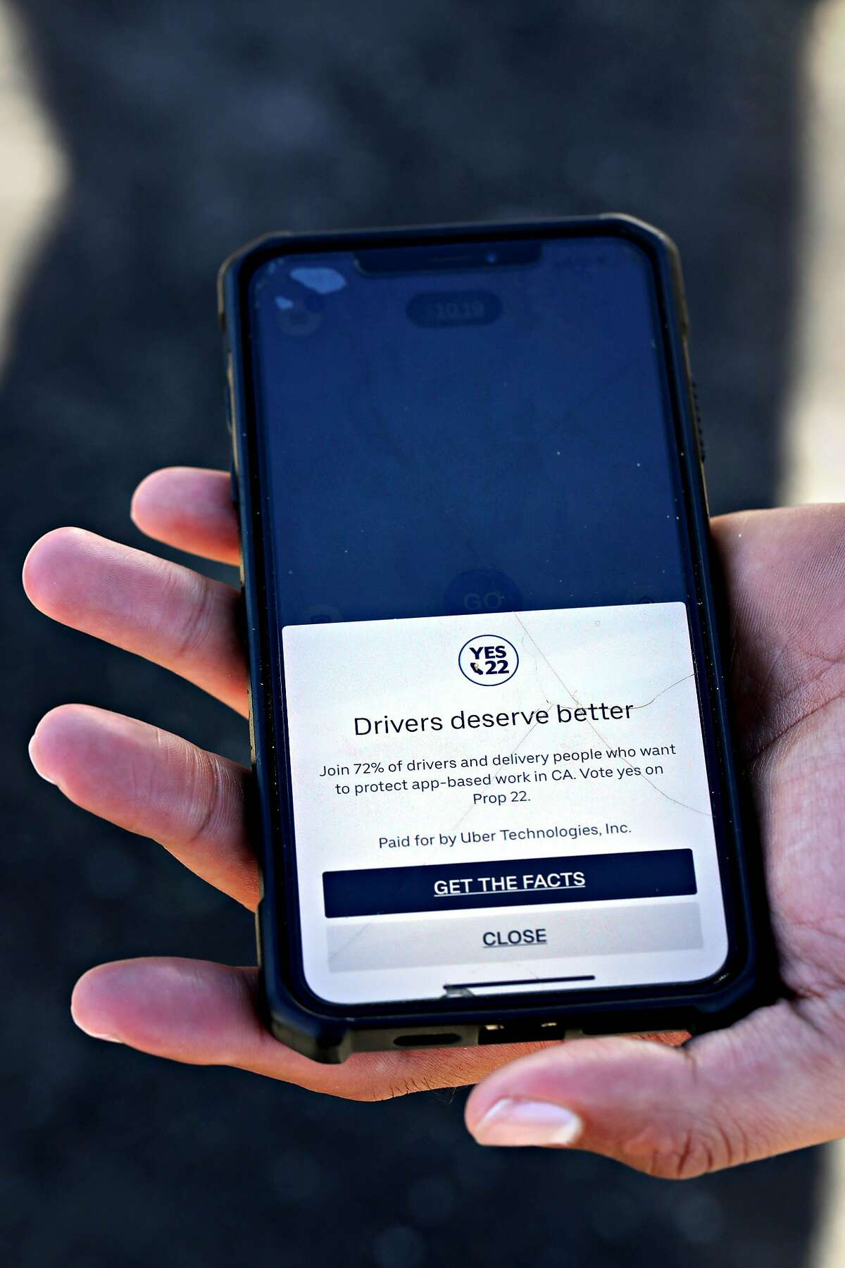 Jorge Torres shows the Prop. 22 ad that he and other Uber drivers see when they open the company's app.