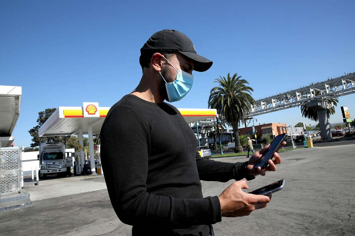 Uber driver Jorge Torres, 29, looks at his phones for ride pickups at a Shell gas station near the Oakland International Airport in October. Uber may end a feature that let drivers see destinations upfront and set pricing for rides.