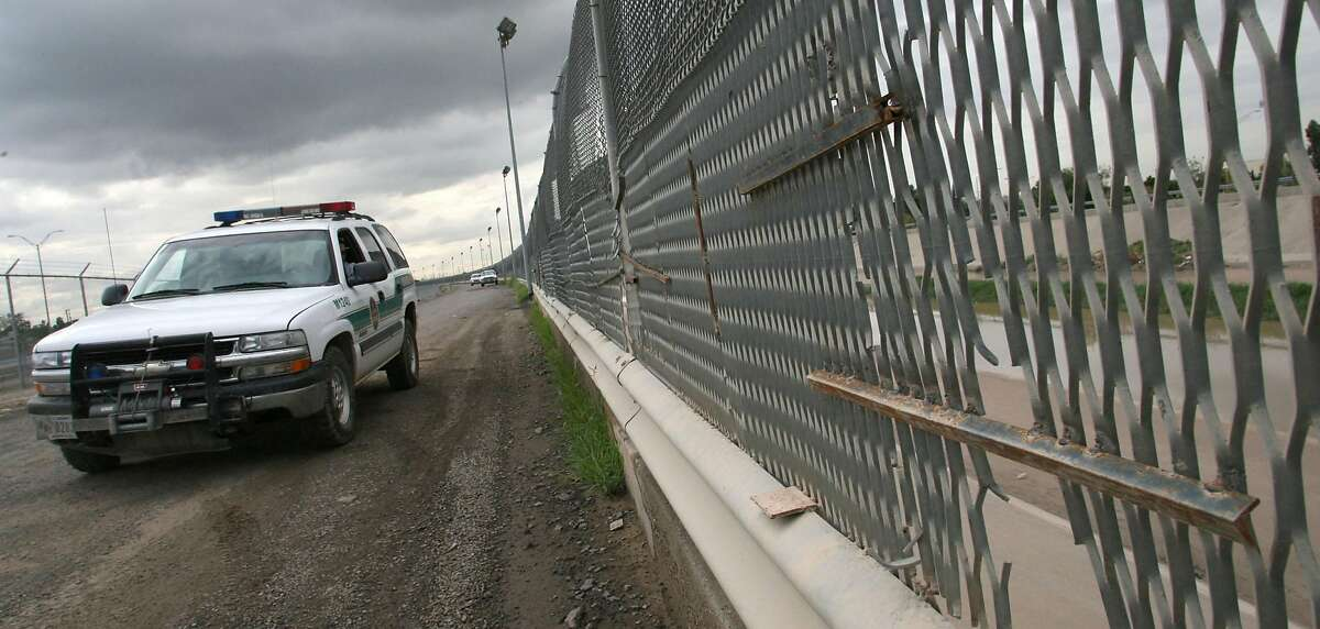 A Border Patrol vehicle drives past a portion of the border fence in El Paso, Texas, in 2007.