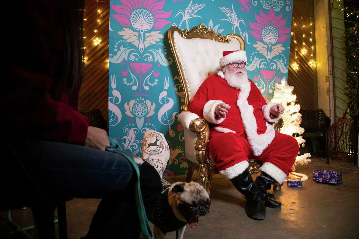 Bryan Taylor gets ready to pose with Double Trouble Caffeine & Cocktails guests for holiday portraits dressed as Santa Claus Thursday, Dec. 19, 2019, in Houston. Don't expect this year's holiday season to look anything like the Thanksgivings and Christmases past.