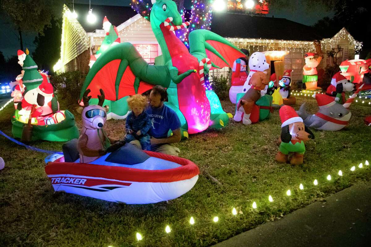 Clay Harrison and his son Marshall Harrison, 3, visit the holiday inflatable figures on their front yard on Friday, Dec. 20, 2019, in Houston. Don't expect this year's holiday season to look anything like the Thanksgivings and Christmases past.