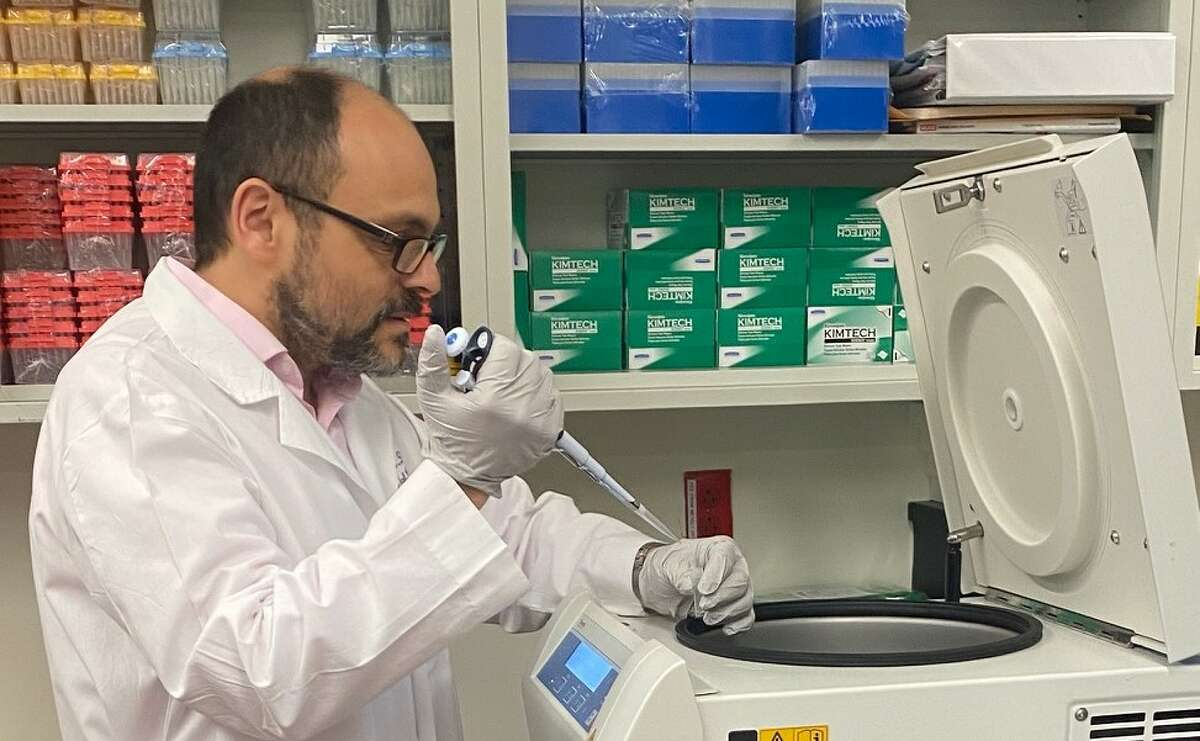 Dr. Ariel Jaitovich, a pulmonary and critical care doctor who has treated some of Albany Medical Center's most severe COVID-19 patients, conducts research at a centrifuge.